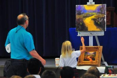 A student helps Greg Cartmell with his painting.